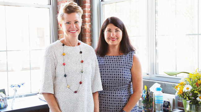 Jules and Joanne standing in their sunlit office of exposed brick and notable office decor Grommet products in the background, with a vase of flowers