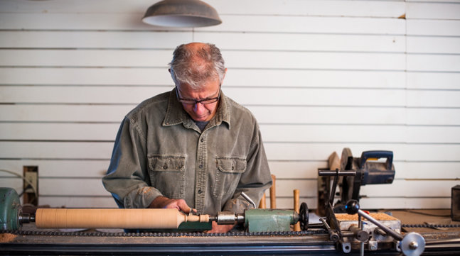 Ken at work on his lathe, cutting the handle of a rolling pin in a tidy shop. His attention is on the work.
