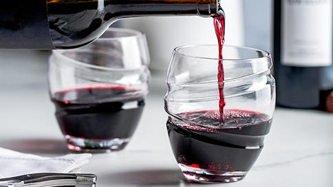 red wine being poured into 2 spinning wine glasses