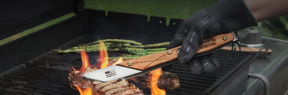 steaks on a grill with tongs
