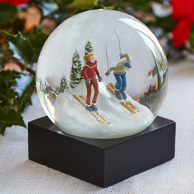 This contemporary snow globe contains a hand painted scene of two people skiing.