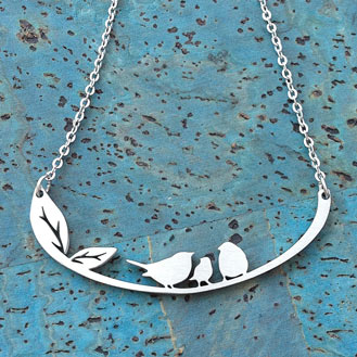 A silver necklace with three birds sitting on a branch.