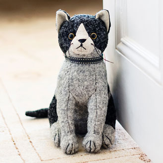 Black, grey, and white felt cat doorstop.
