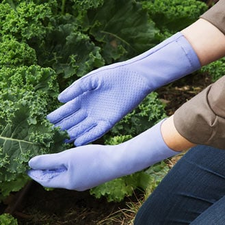 Person wearing elbow-length gloves in a garden.