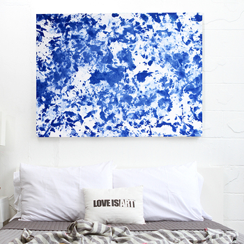 A blue and white abstract painting hangs on the wall above a bed.