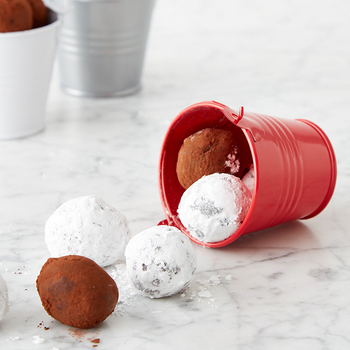 Dark and white chocolate truffles roll out of a red tin across the counter.