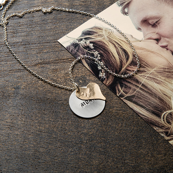 A custom heart necklace rests on a photograph of a kissing couple.