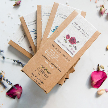 Five small batch chocolate bars fan out on a counter sprinkled with rose petals and lavendar.