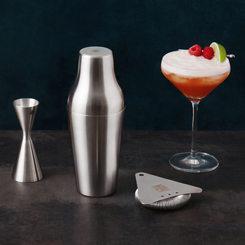 A frothy pink cocktail stands beside a stainless steel mixing set.