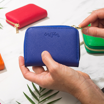 Hands upzip a small, brightly colored wallet.