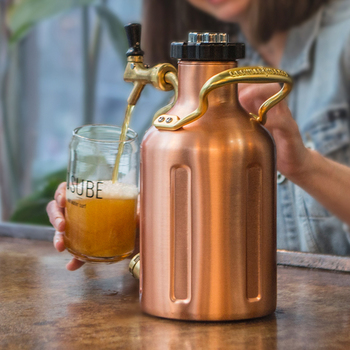 A smiling person fills their glass with beer from an easy pour tap on this copper keg.