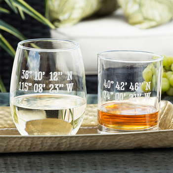 A stemless wine glass and a rocks glass sit on a tray, both sand etched with latitude and longitude coordinates.